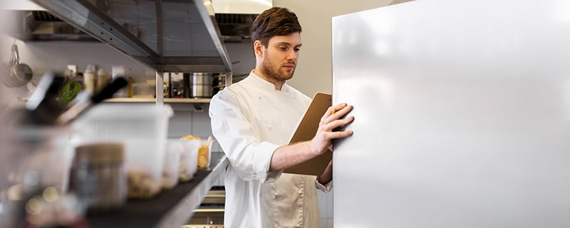 A chef consulting a clipboard while looking through a refrigerator